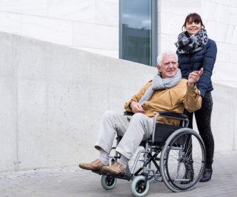 couple helping senior man to sit in wheelchair