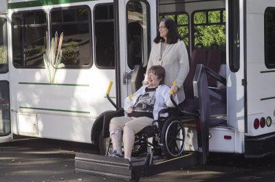 a senior woman in a wheelchair helped off a van using a chair lift