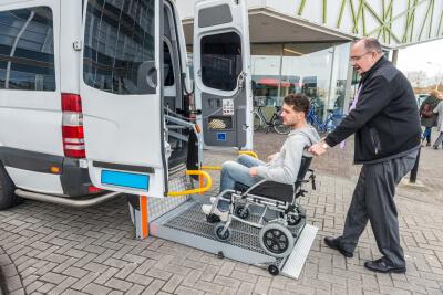 a driver assisting a man on a wheelchair