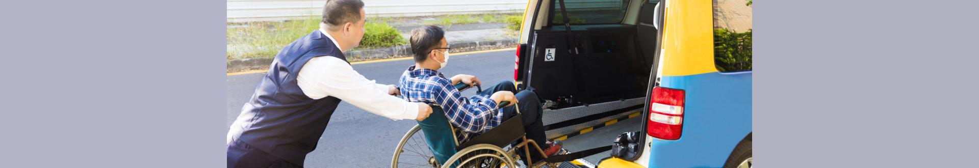 man assisting senior man to get into van